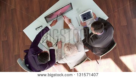 Managers discussing presentation on computer monitor