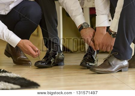 Groom and groom mates tying the shoes .