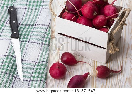 Knife and red radishes in a wooden box on wooden desk