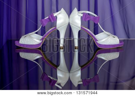 Bride's white and purple shoes on a table with reflection.