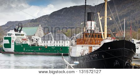 BERGEN, NORWAY - MAY 15, 2012: Stord I retro ship and modern tugboat Bourbon Orca at pier in port of Bergen