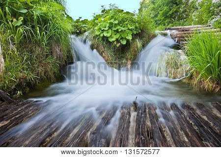 Two small waterfalls with plants in Plitvice park