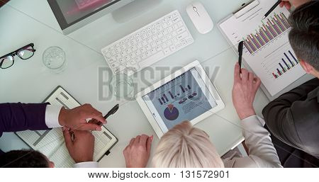 Three managers analyzing data on spreadsheet
