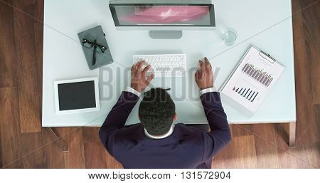 Male manager using computer during his usual workday