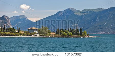 Coastal view of Garda lake with mountains, trees, buildings