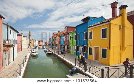 VENICE, ITALY - JUNE 28, 2013: Tourists are walking along one of the channels of Burano island