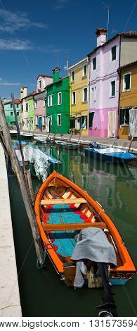 VENICE, ITALY - JUNE 28, 2013: Bright boat in the channel of the Burano island. Venice, Italy