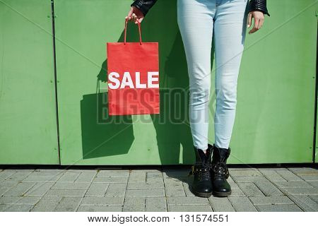 Female legs and shopping bag in hands