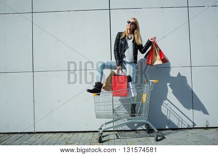 Woman posing with shopping bags in trolley cart