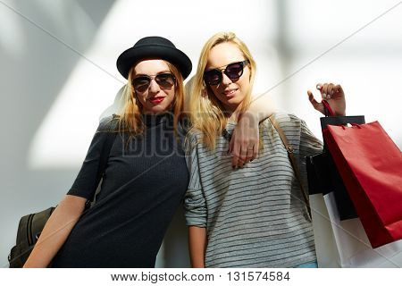 Portrait of two stylish women with shopping bags