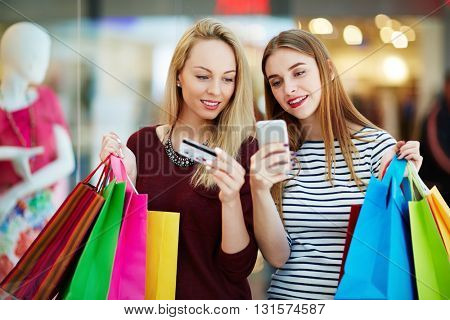 Women reading sms in shopping mall
