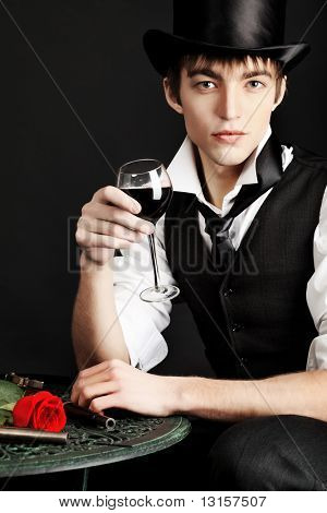 Portrait of a young gentlemen wearing dinner jacket and black top hat. Shot in a studio.