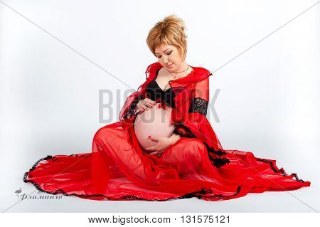 Young pregnant woman in red clothes looks at her stomach, she is happy
