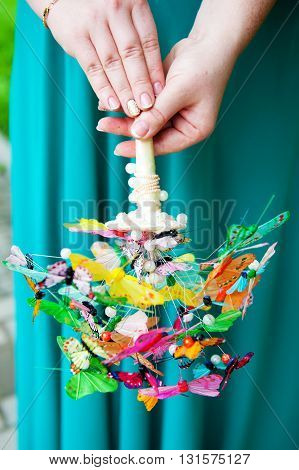 Beautiful bouquet of colorful butterflies in the hands of the young woman bride