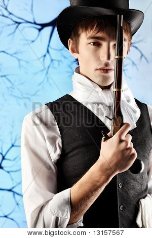 Portrait of a young gentlemen in a jacket and  top hat holding gun in his hand. Shot in a studio.