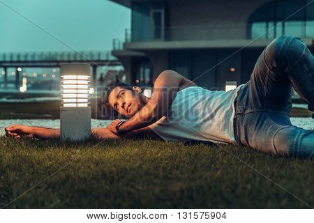 Stylish man in the white T-shirt, leather jacket and jeans posing lie on the floor near lamp