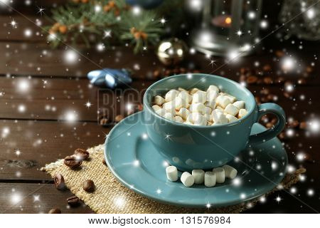 Mug of hot chocolate and marshmallows on wooden background with snow effect