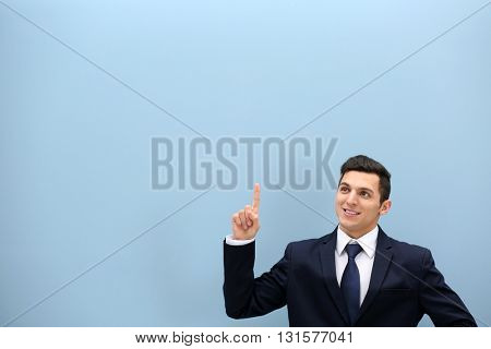 Attractive young man in a suit against light blue wall