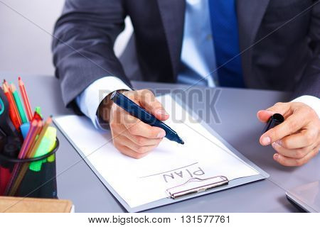 Young businessman working in office, sitting at a table.