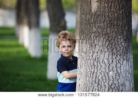 Little curly boy is hiding behind a tree