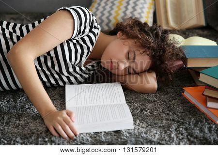 Beautiful girl sleeping on carpet with books