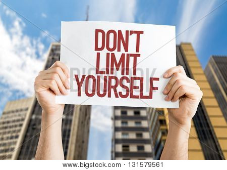 Don't Limit Yourself placard with urban background