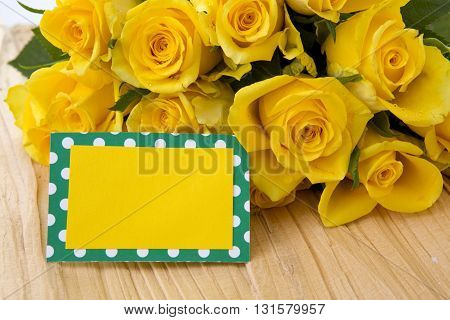 Mothers day greeting card or photo frame and yellow rose over wooden table.