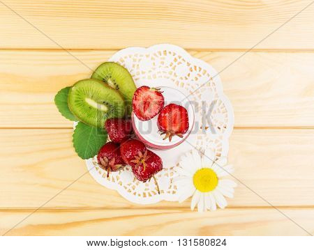 A bowl of pureed fresh strawberries, kiwi slices, napkin in the background light wood.