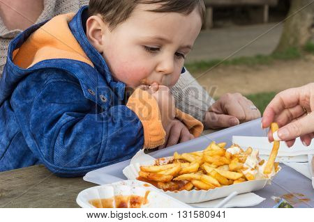 Child eats sausage with french fries from a paper plate.