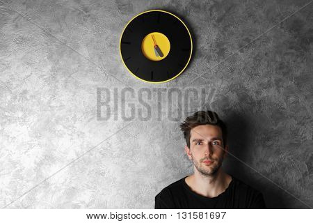 Man in a black shirt standing beside a  big clock on grey wall