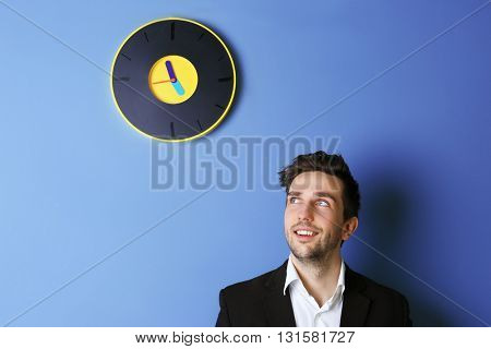 Man in black suit standing beside a  big clock on blue wall