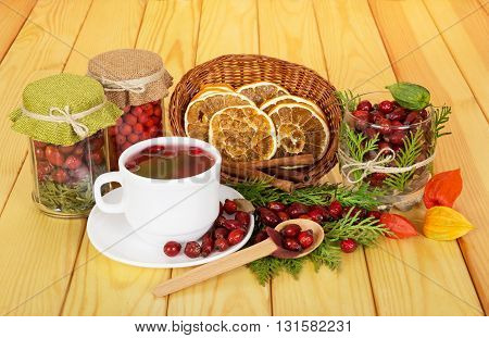 Banks rowan berries, rose hips, tea cup, bowl with slices of lemon and cinnamon sticks in the background light wood.