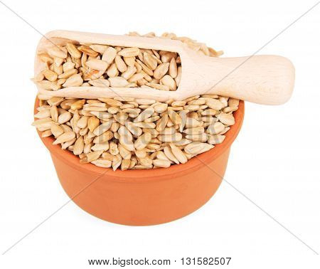 A bowl and a wooden scoop with peeled sunflower seeds isolated on white background.