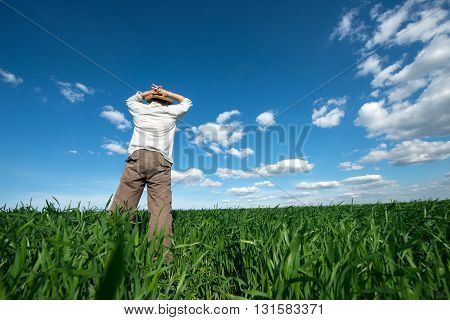 young man on green field of wheat
