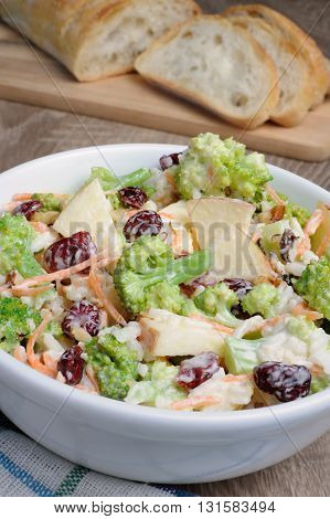 Salad of broccoli carrots apples rice cranberries and walnuts dressed with yogurt