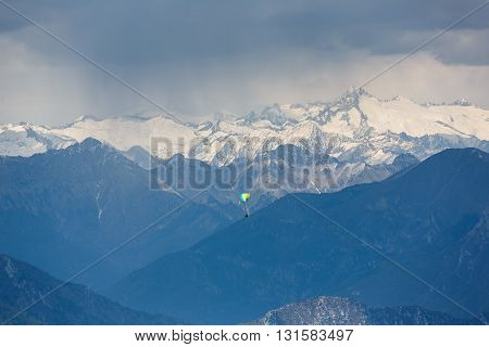 Paraglider flying over the Lake Garda in the Dolomite mountains