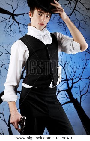 Portrait of a young gentlemen in a jacket top hat holding gun in his hand. Shot in a studio.