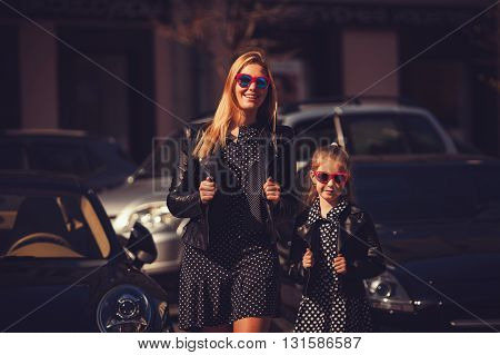 fashion family. woman with child girl in family fashionable look outdoor. Fashion young mother and child daughter wearing a sunglasses