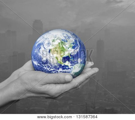 Earth in black and white hands over pollution city Environment concept Elements of this image furnished by NASA