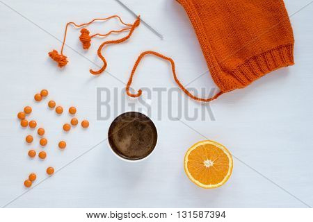 Cup of coffee, orange, candies and a woolen knitted hat on white background.