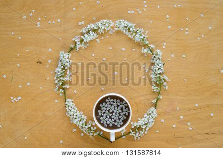 Coffee and twigs of blooming bird cherry laying out in circle on wooden board.