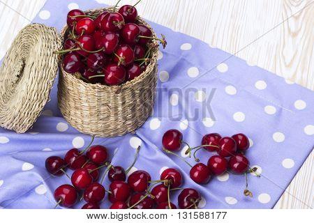 Cherry basket on the white wooden desk