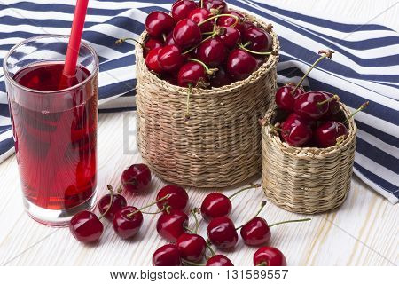 Cherry baskets and juice on the white wooden desk