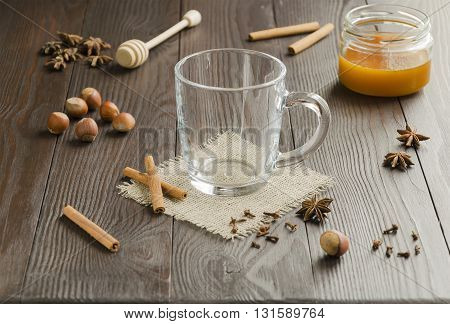 Empty glass cup with cinnamon sticks on a linen napkin with honey nuts and spice