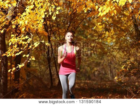 Young beautiful woman jogging in autumn park