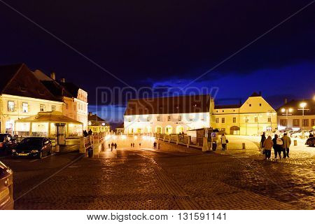 SIBIU, ROMANIA - MARCH 08, 2016: Photo of city houses at central street in the night, at the woman's day celebration