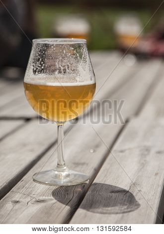 A glass of draught blonde beer on a wooden table