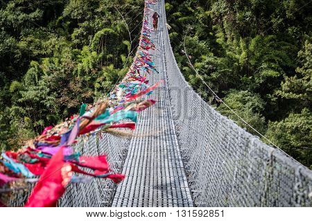 Ghasa, Nepal - November 05, 2014: Nepalese woman crossing a suspension bridge on the Annapurna Circuit.