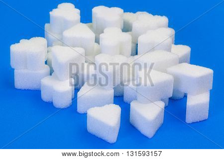 Sugar cubes in various forms in blue backgrounds .