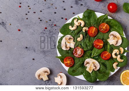 Salad with spinach mushrooms cashew nuts and tomatoes on concrete background top view copy space.